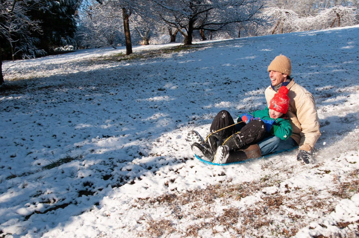Smiling young man and small boy in a red toboggan sledding on thin covering of snow on a sunny morning
