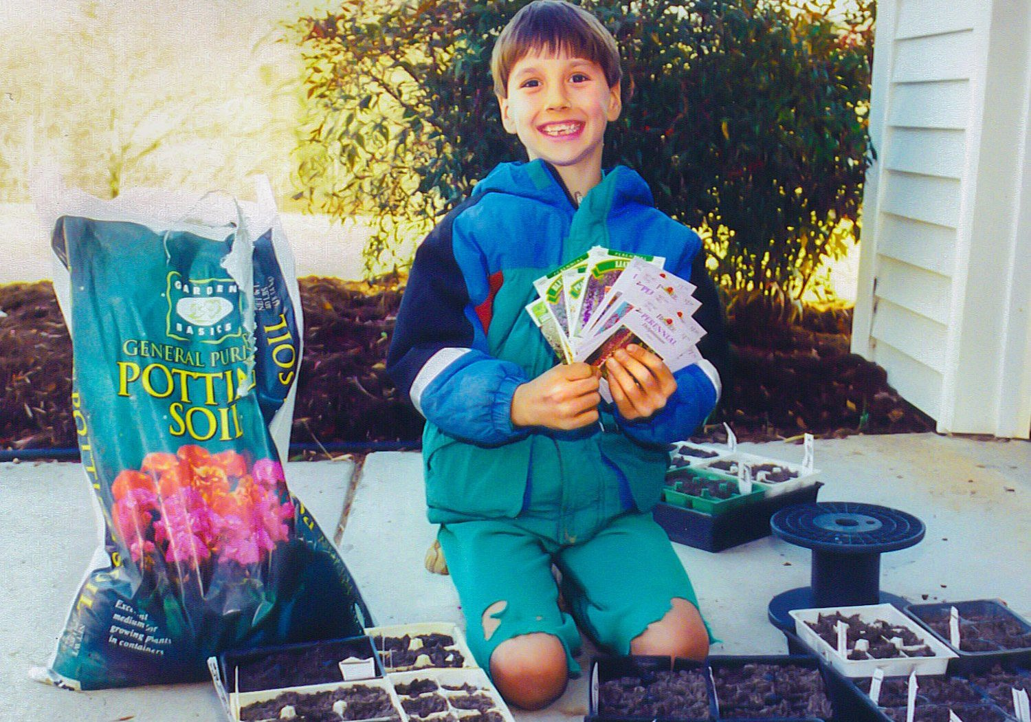 Young boy kneeling as he proudly displays a fanned out display of flower seed packets